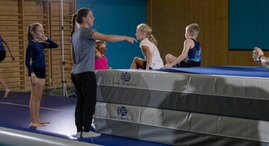 Une enseignante donne des instructions à des enfants assis sur deux gros tapis.