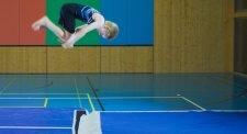 Ein Schüler macht einen Salto vorwärts