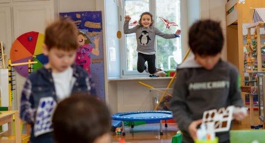 Une enfant saute sur un trampoline de fitness pendant que des camarades effectuent une tâche manuelle à une table.