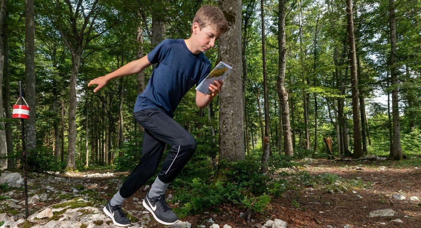 Junger Athlet beim OL im Wald.