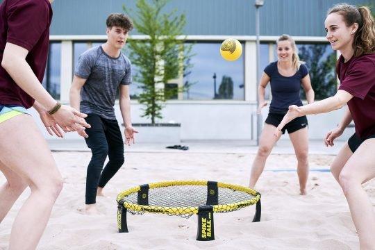 Vier Jugendliche spielen Roundnet.
