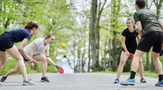 Quattro ragazzi giocano con una pallina e quattro racchette su una strada di campagna