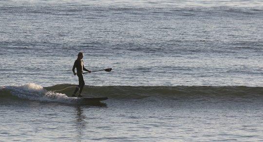 Photo: un pagayeur attend la vague.