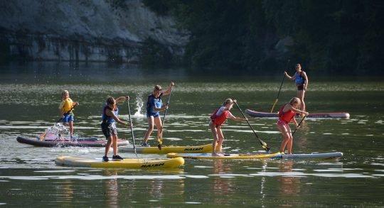 Fünf Kinder und eine Leiterperson am Paddeln auf dem See.