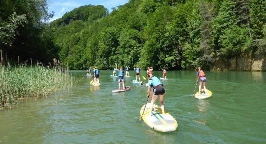 Kinder und Leiterperson beim Paddeln auf dem Fluss.