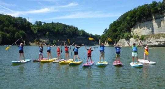 Foto: Mehrere Kinder und Leiter auf einer Reihe im Wasser strecken die Arme in die Höhe.