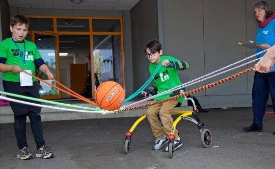 Zwei Kinder - eins im Rollstuhl - bei einem gemeinsamen Spiel.