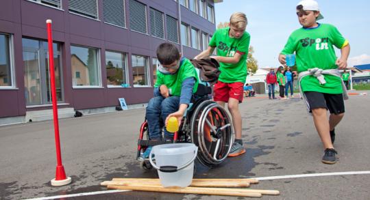 Trois enfants, dont un en fauteuil roulant verse le contenu de leur gobelet dans un seau.