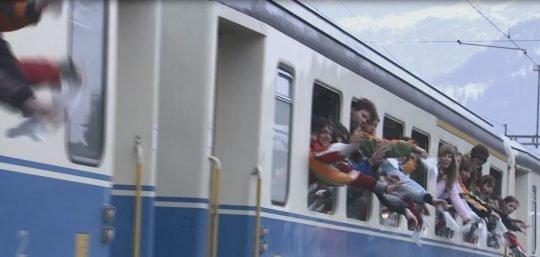 Foto: Fahrender Zug, Jugendliche schauen zum Fenster raus.