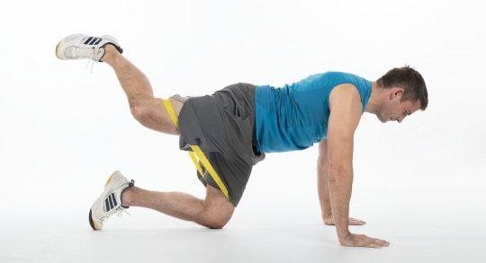 Un jeune homme effectue un exercice de renforcement musculaire avec un mini-band.