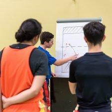 Foto: Schüler erklärt Kollegen die Teamtaktik an Flipchart.