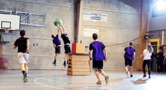 Des jeunes jouent au Poull Ball dans une salle de sport.