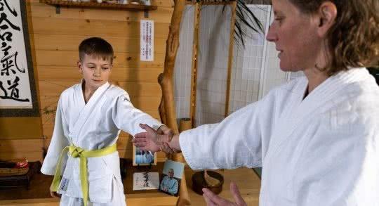 Lehrperson bei einem Aikido-Griff mit einem jungen Schüler.