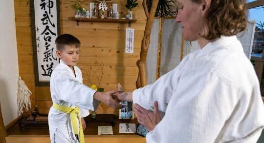 Un enfant réalise un exercice d'aïkido avec un enseignant.