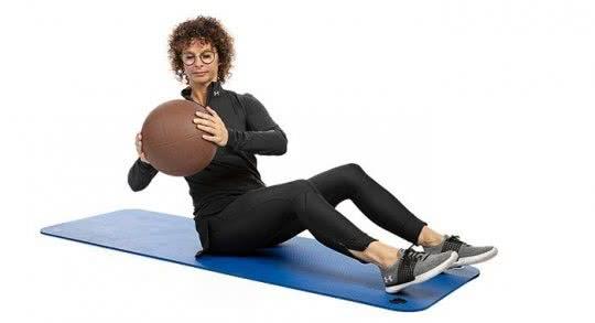 Claudia Romane effectue une rotation du tronc en position assise avec le médecine-ball.