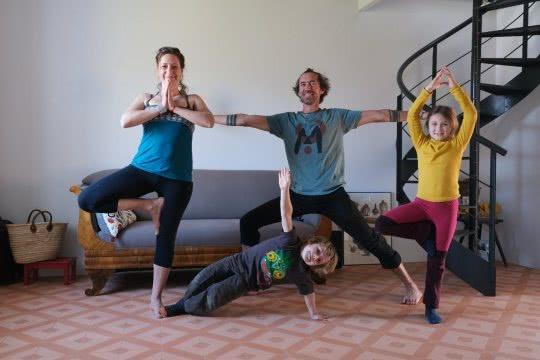 Une famille exécute des postures de yoga.