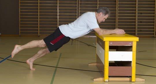 Un adulte effectue un exercice de renforcement en appui sur un banc.