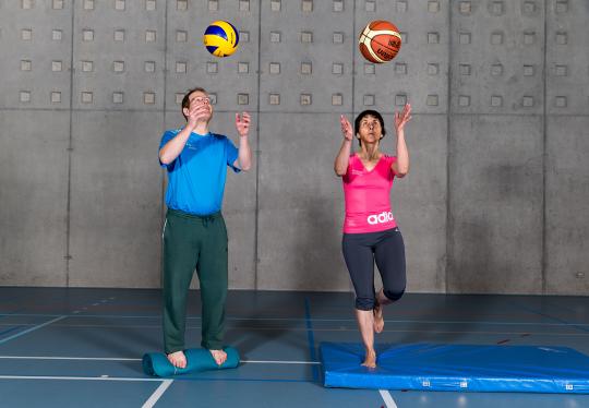 Deux adultes lancent et rattrapent un ballon debout sur un support instable.