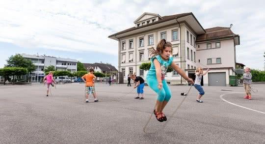 Des enfants sautent à la corde dans une cour d'école.