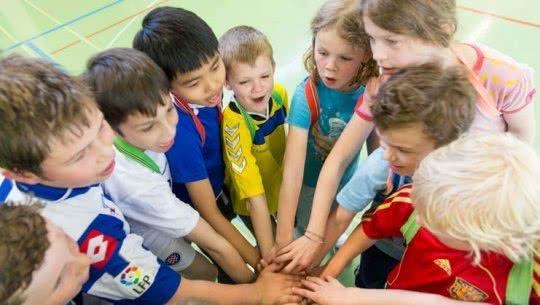 Des enfants sont en cercle tendent leur main vers le centre.