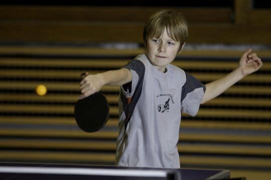 Un jeune garçon joue au tennis de table.