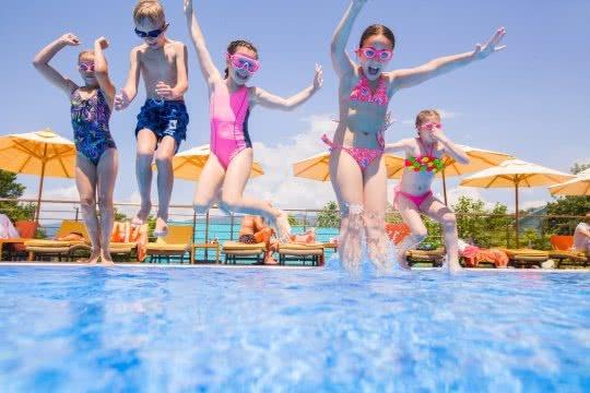 Des enfants sautent dans une piscine depuis le bord.