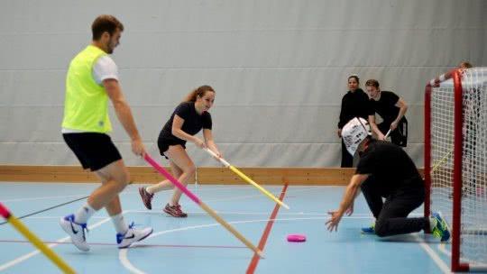 Jung Frauen und Männer beim Donut Hockey Spiel vor dem Tor.