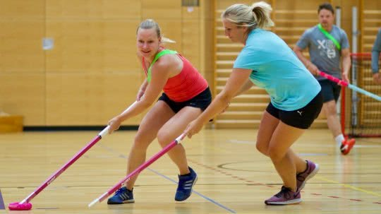 Frauen und Männer beim Donut-Hockey-Spielen.