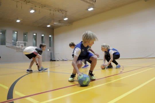 Des enfants jouent avec des balles dans une salle de sport.