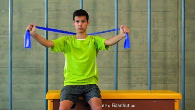 Jugendlicher bei einer Übung mit dem Mini-BAnd- während er auf einem Schwedenkasten sitzt.