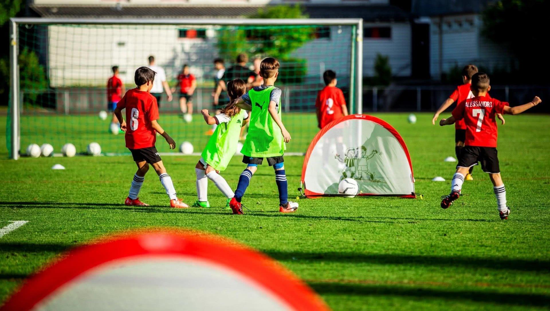 Des enfants jouent sur un petit terrain de football.