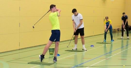Quatre jeunes entraînent le swing dans une salle de sport.
