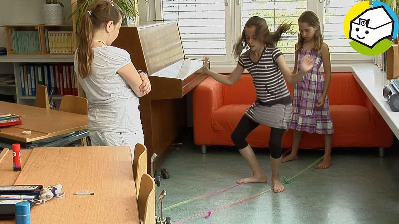 Drei Mädchen beim Gummitwist im Schulzimmer.