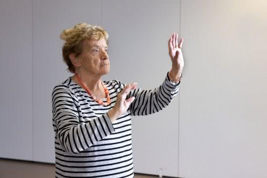 Eine ältere Dame führt eine Pantomimen-Übung aus.