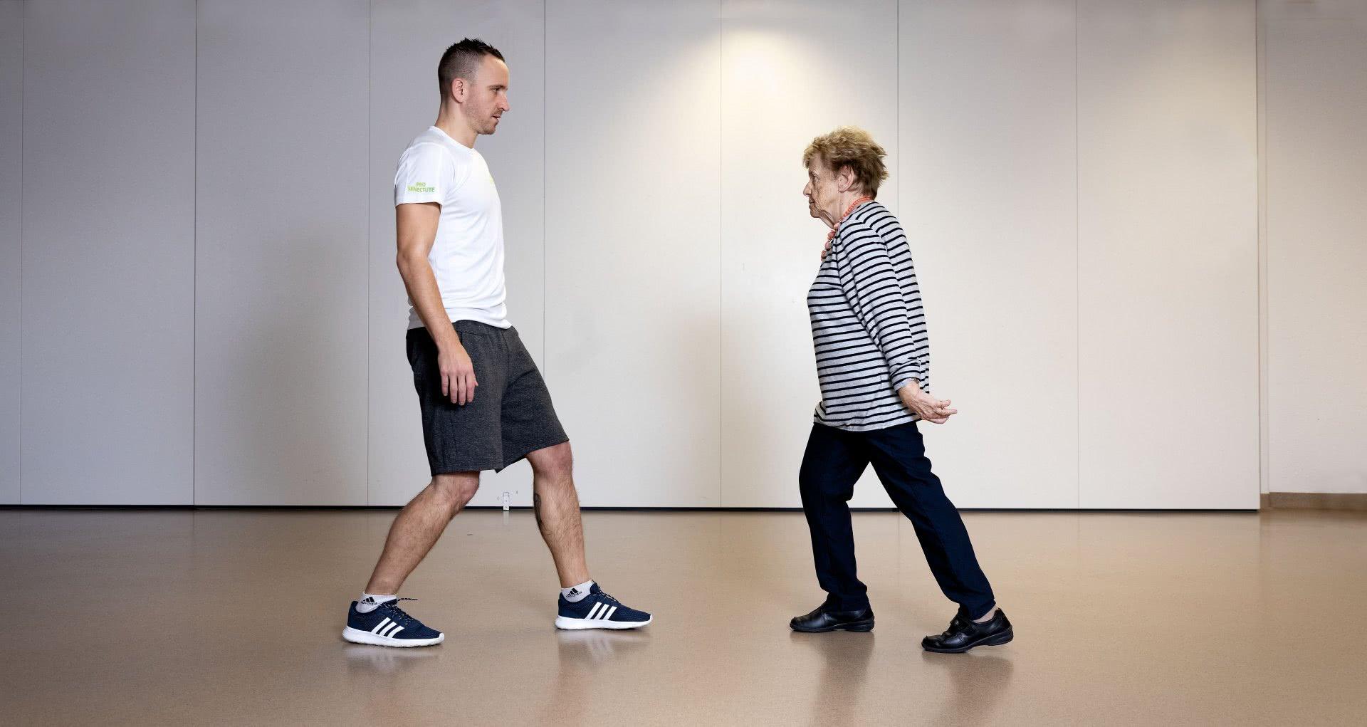 Un monitore e una signora anziana durante un esercizio nel corso di una lezione DomiGym