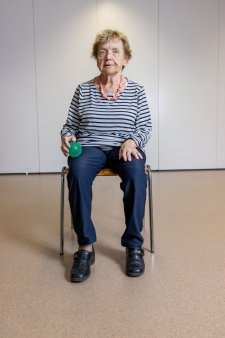 Auf einem Stuhl sitzend massiert sich eine eine betagte Frau den  Oberschenkel mit einem Igelball.