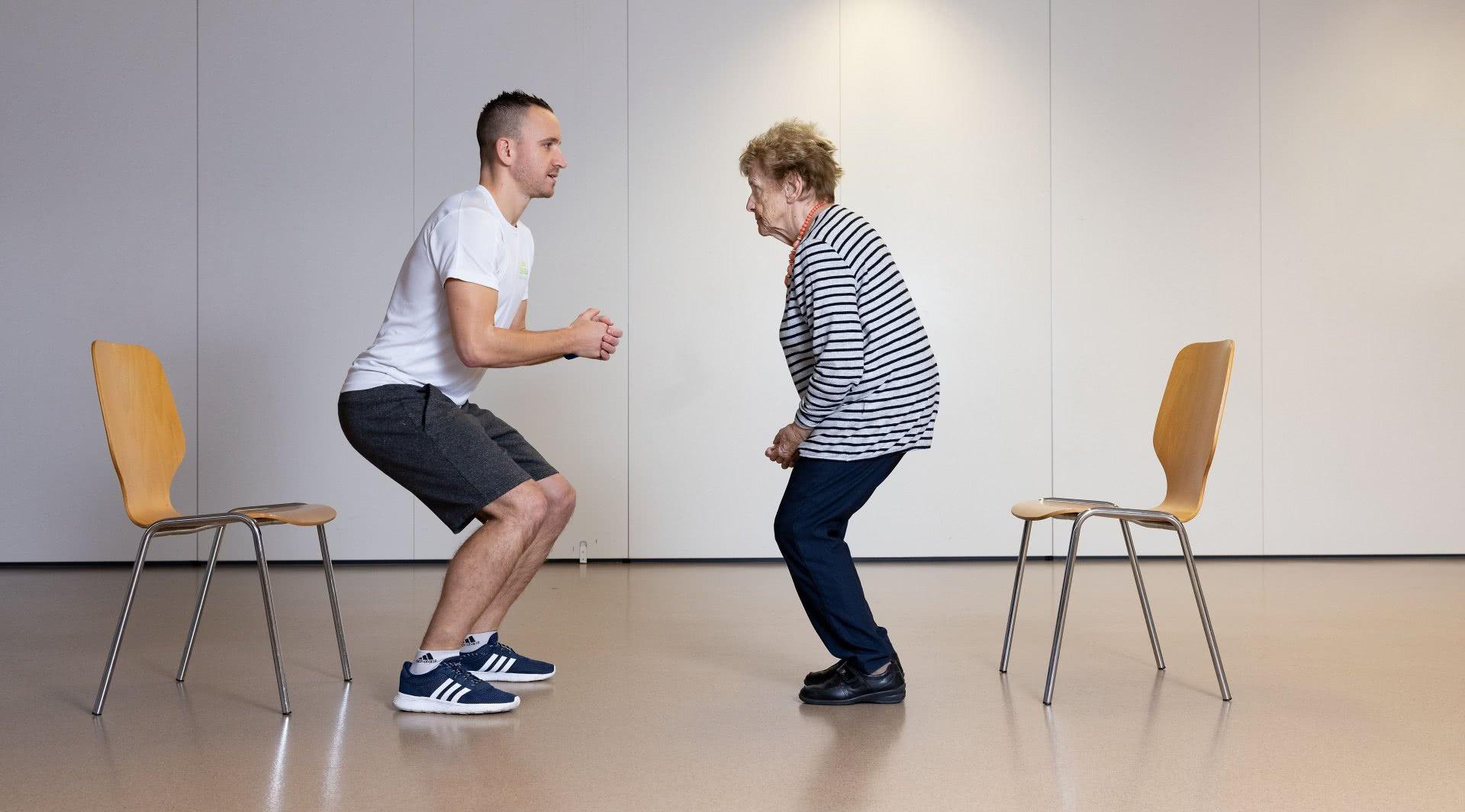 Un monitore e una persona anziana eseguono un esercizio in modo speculare