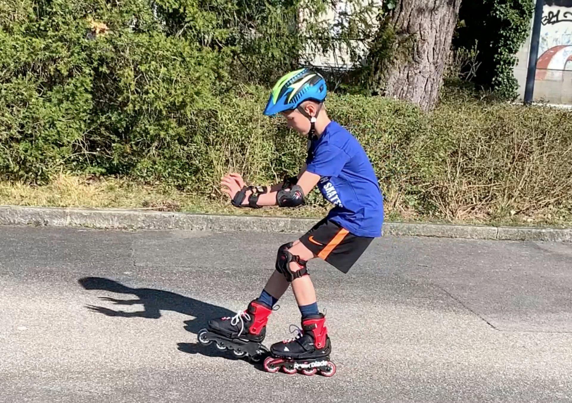 Kind beim Bremsen auf Inline-Skates.