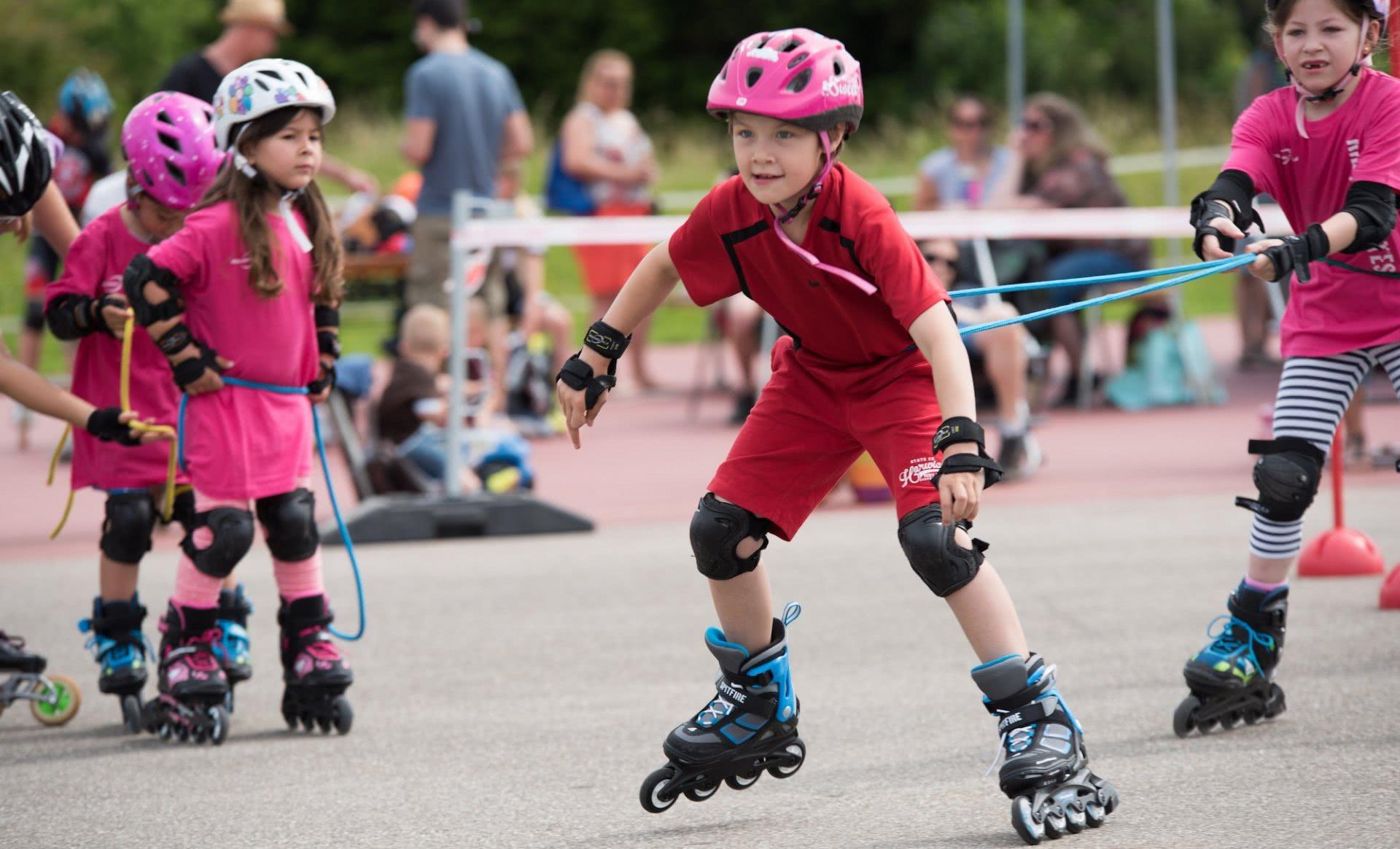 Ein Mädchen auf Inline-Skates zieht ein anderes mit einem Seil.