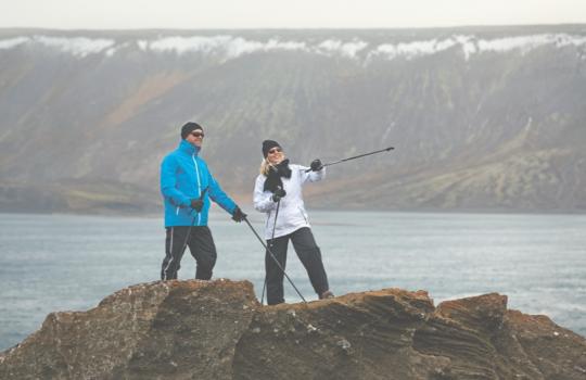 Un uomo e una donna in abiti sportivi invernali durante un allenamento di Nordic walking