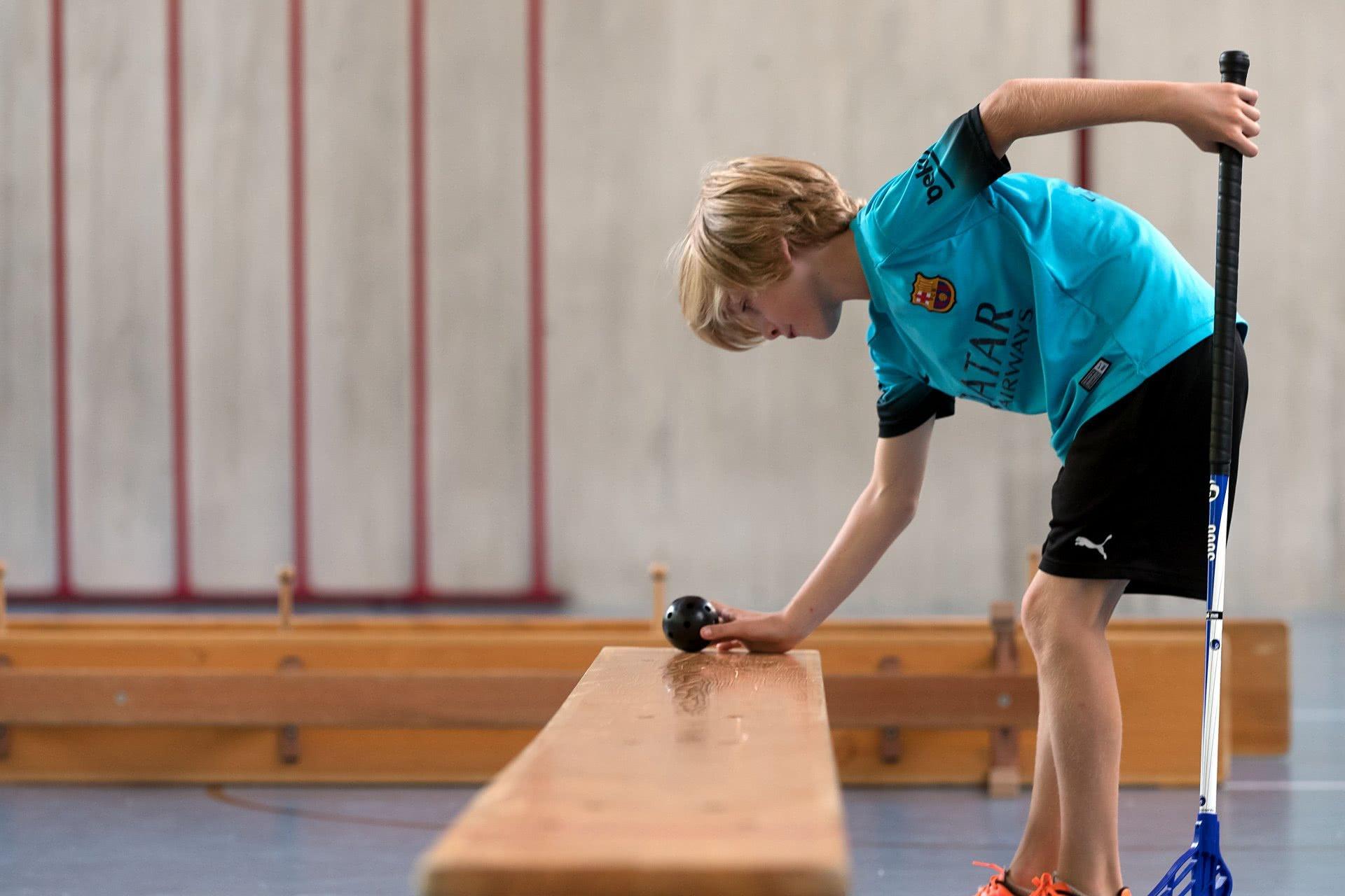 Un enfant pose une balle de minigolf sur un banc suédois.