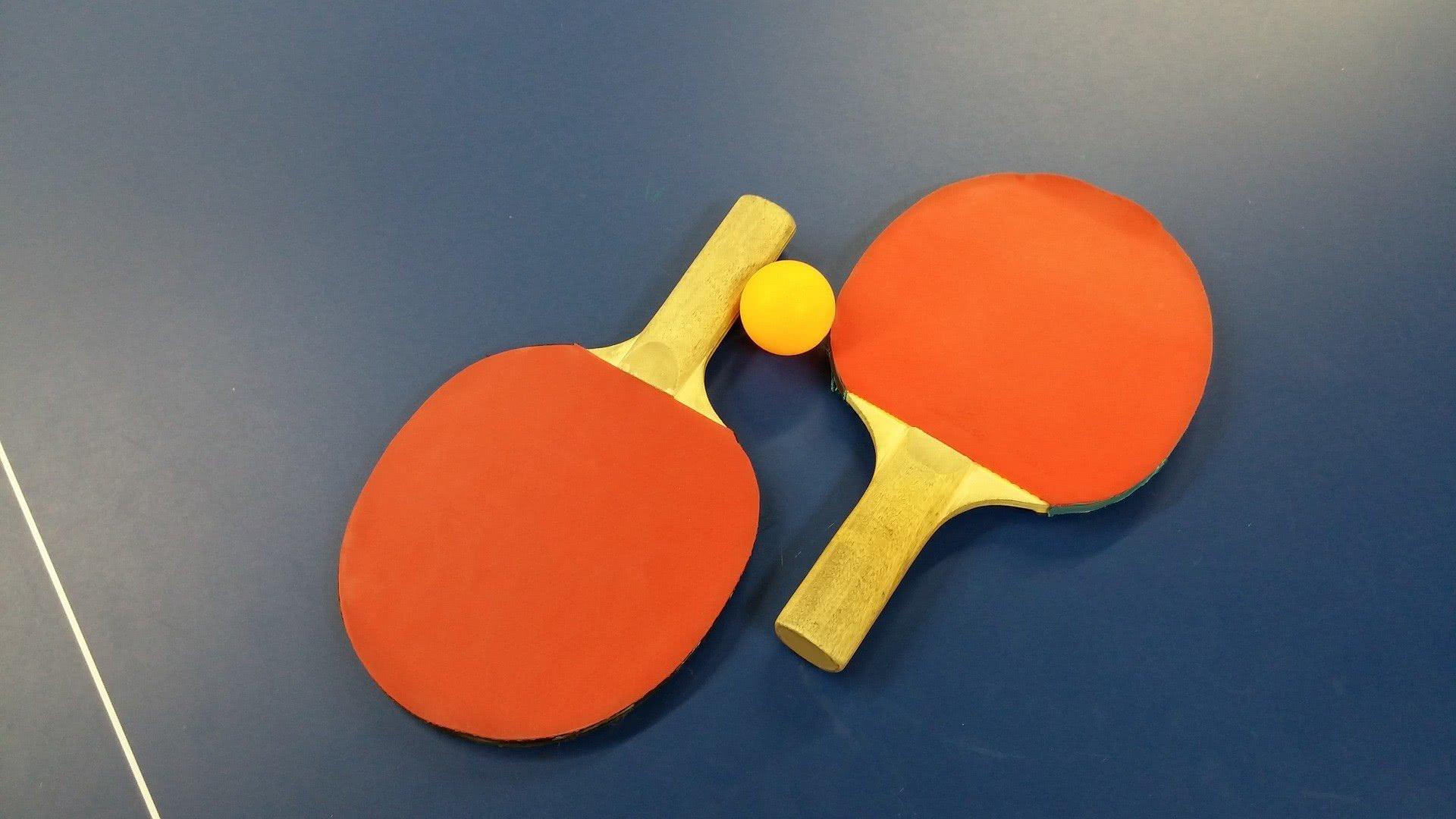 Due racchette da tennistavolo arancioni e una pallina gialla su un tavolo da ping pong blu