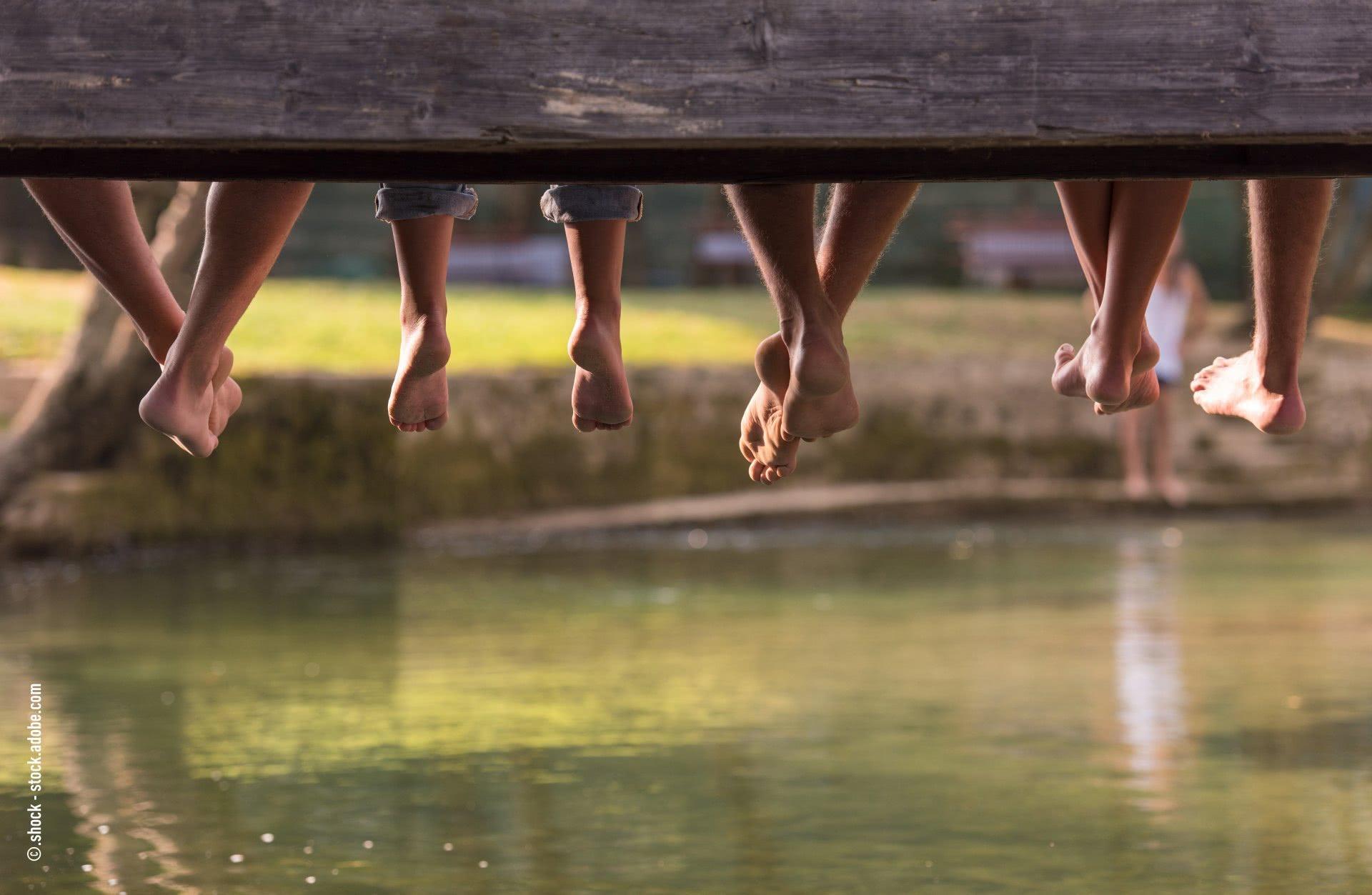 Baumelnde Füsse über Wasser.