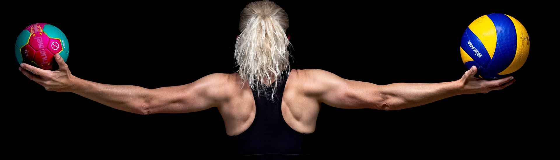 Foto: Rückenansich - Athletin balanciert zwei verschieden grosse Bälle mit seitlich ausgestreckten Armen.