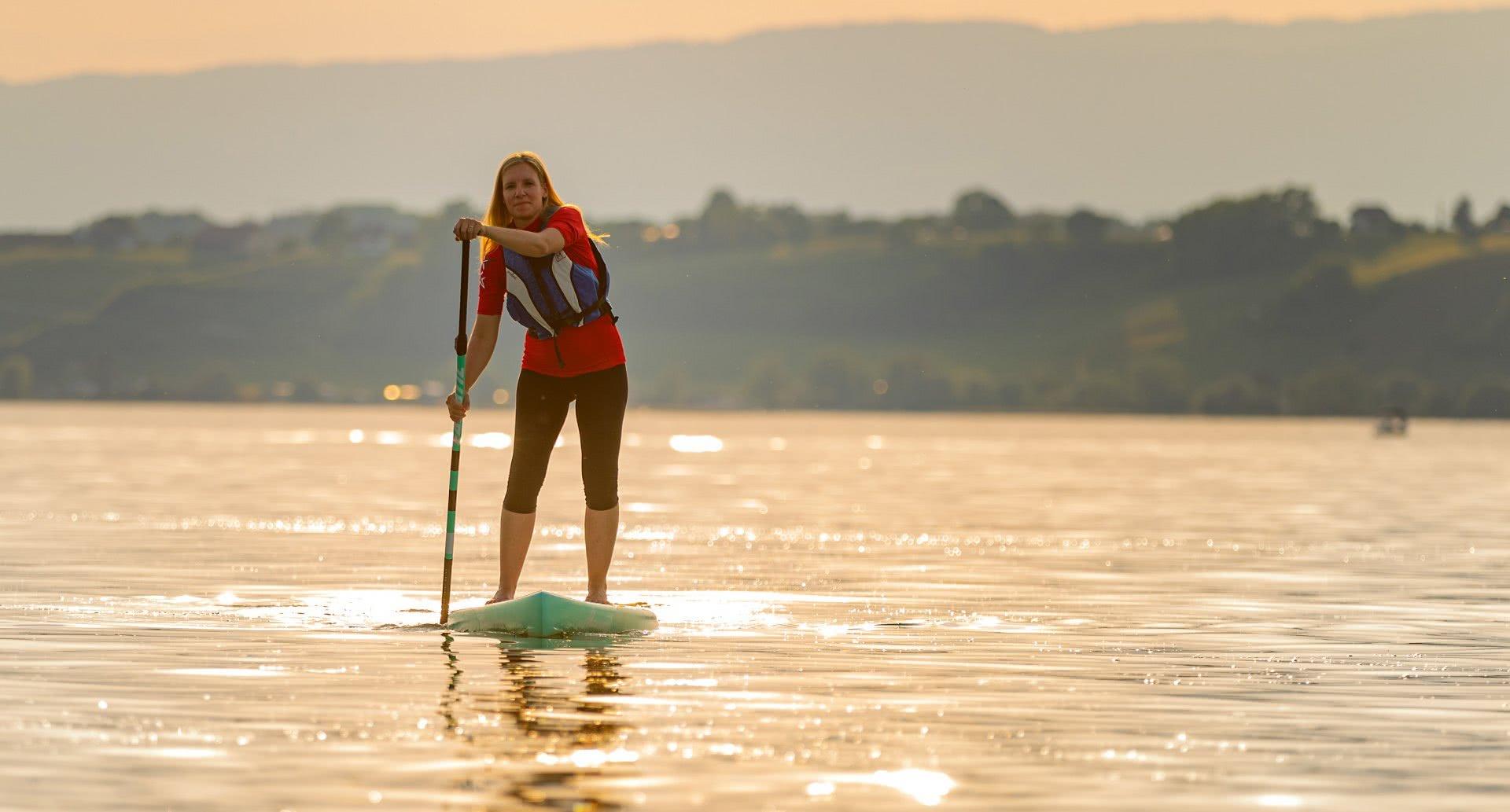 Una donna su un paddle avanza sull'acqua di un lago al tramonto