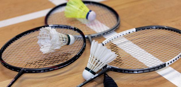 Raquettes de badminton posé sur le sol avec un volant sur le tamis