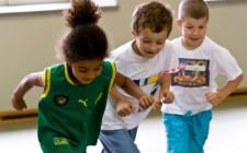 Kinder rennen, sich an den Armen haltend.