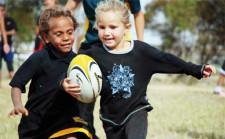 Due bambine corrono una accanto all'altra cercando di rubarsi il pallone.