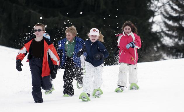 Un gruppo di bambini che indossano abiti invernali e racchette da sci ai piedi corrono nella neve