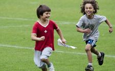 Zwei Kinder rennen auf einer Wiese hintereinander her.
